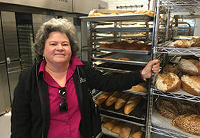 Betty Porto in front of the Porto's Bakery Bread Rack